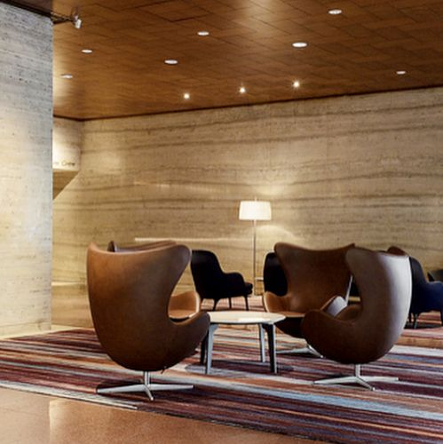 Seating area with Arne Jacobsen's Egg™ chairs from Fritz Hansen crafted with brown Sørensen Leather.