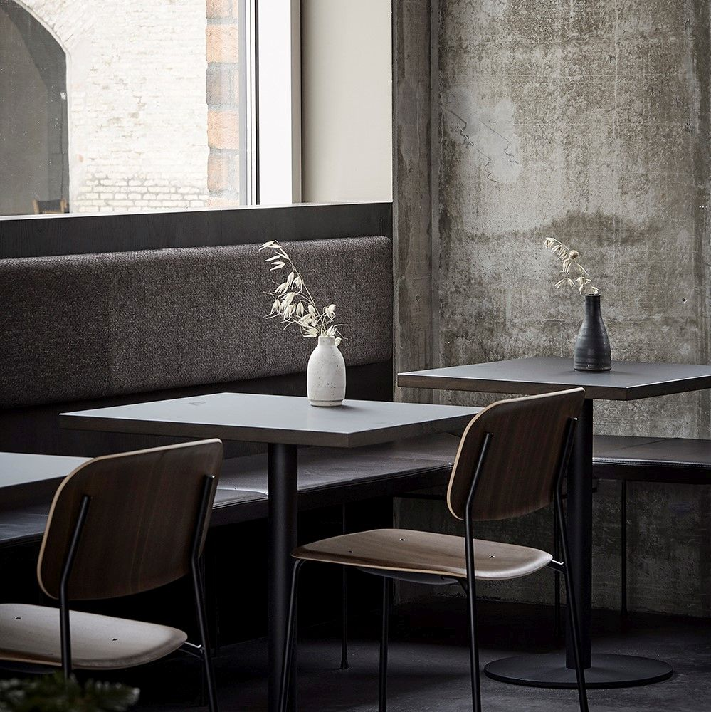 Cosy restaurant corner with concrete walls and bench seats in black leather