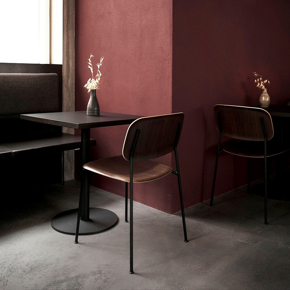 Cosy restaurant corner with red walls, concrete floor and bench seats crafted with black leather
