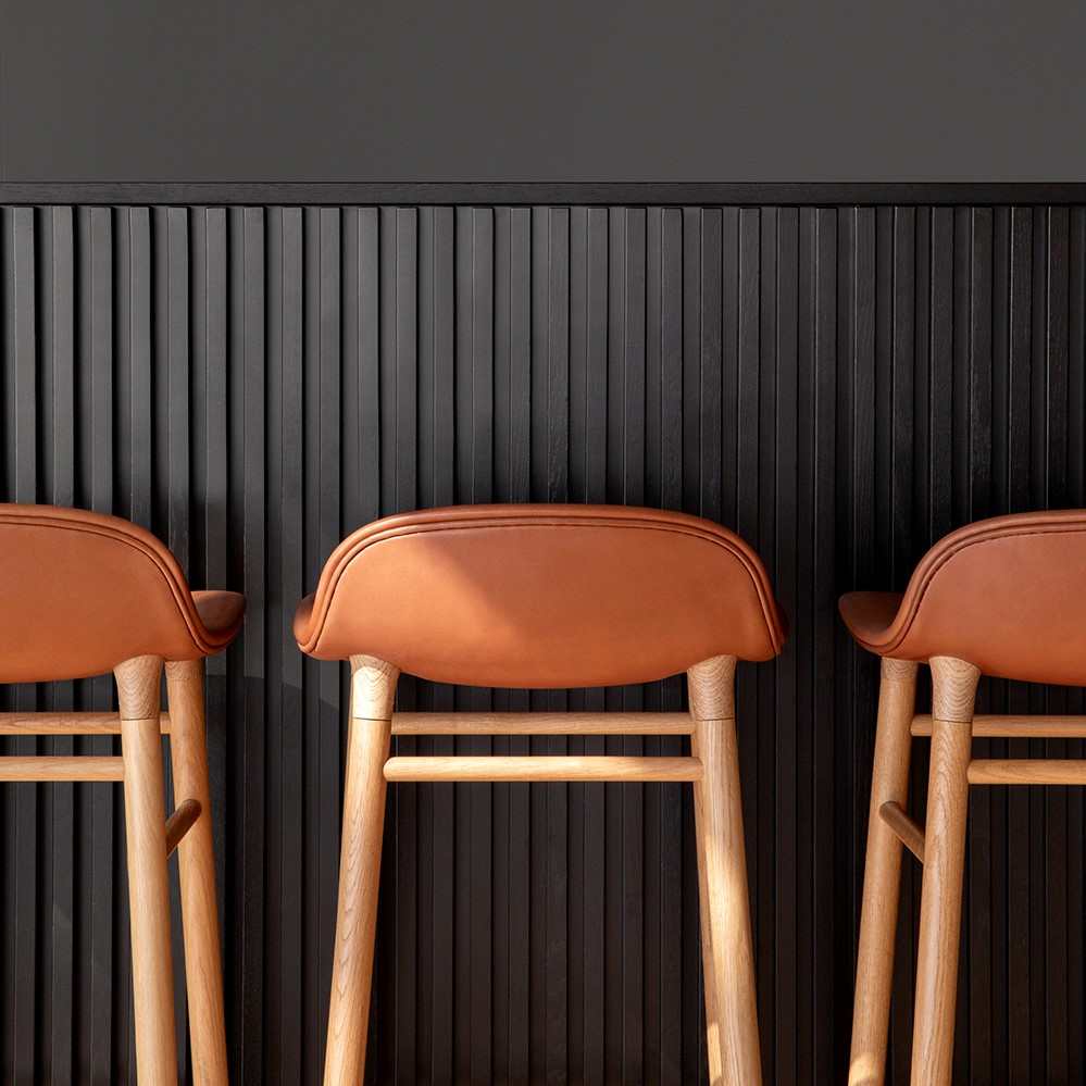 Details of bar stools with brown leather seats and wooden legs