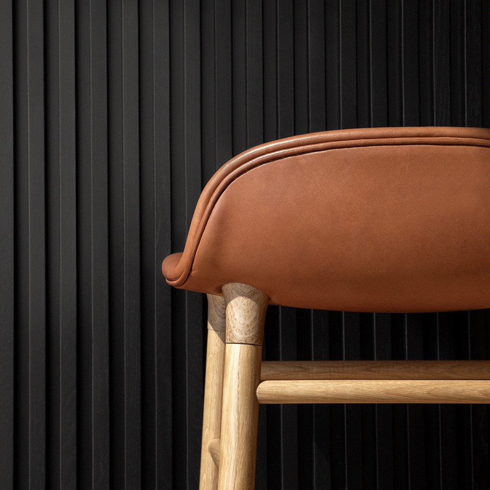 Details of a bar stool with a brown leather seat and wooden legs
