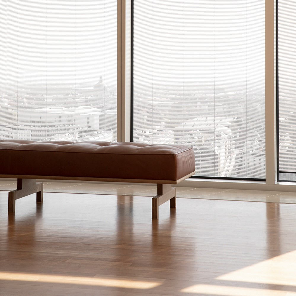 Brown leather daybed with wooden legs next to a window with a city view