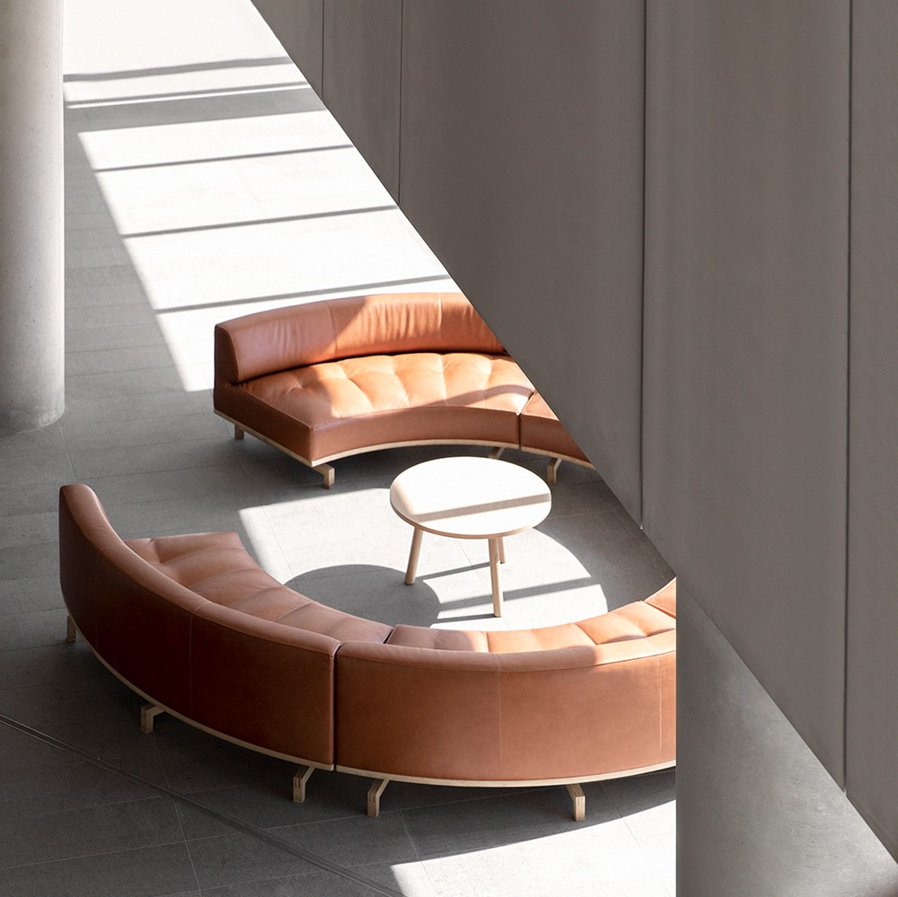 Round, brown leather sofa inside industrial building