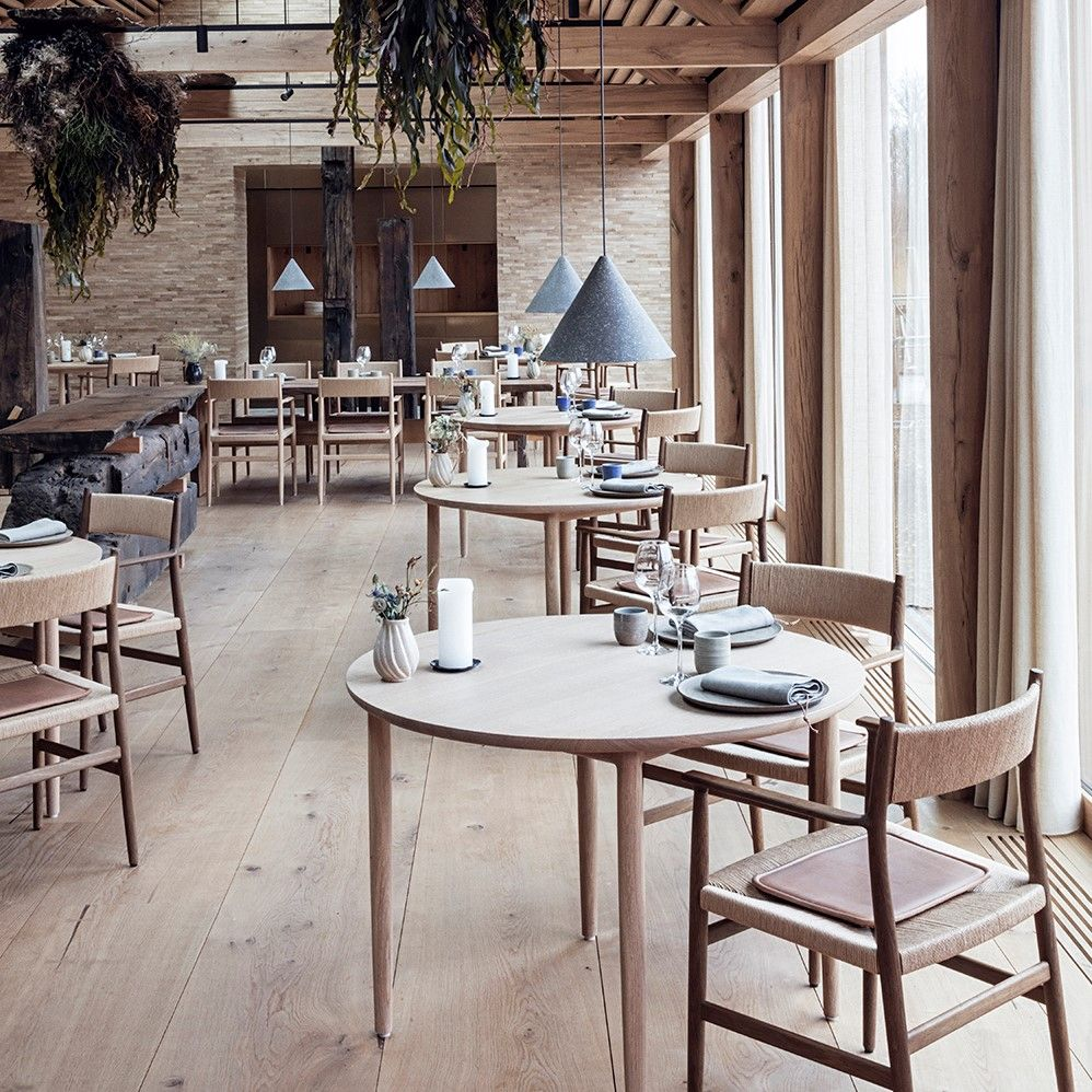 Restaurant interior with wooden tables and chairs featuring cushions crafted with Sørensen Leather DUNES