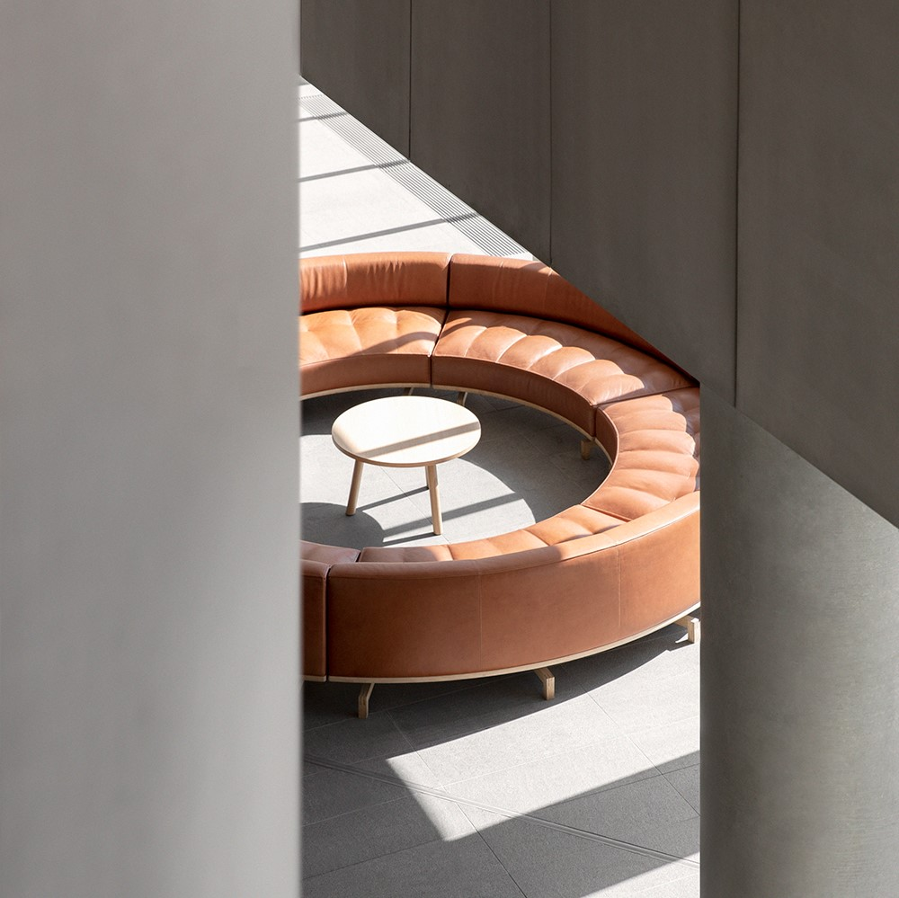 Round, brown leather sofa inside concrete building