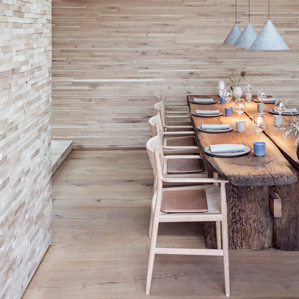 Cosy restaurant setting with a wooden table and chairs featuring cushions crafted with Sørensen Leather DUNES.