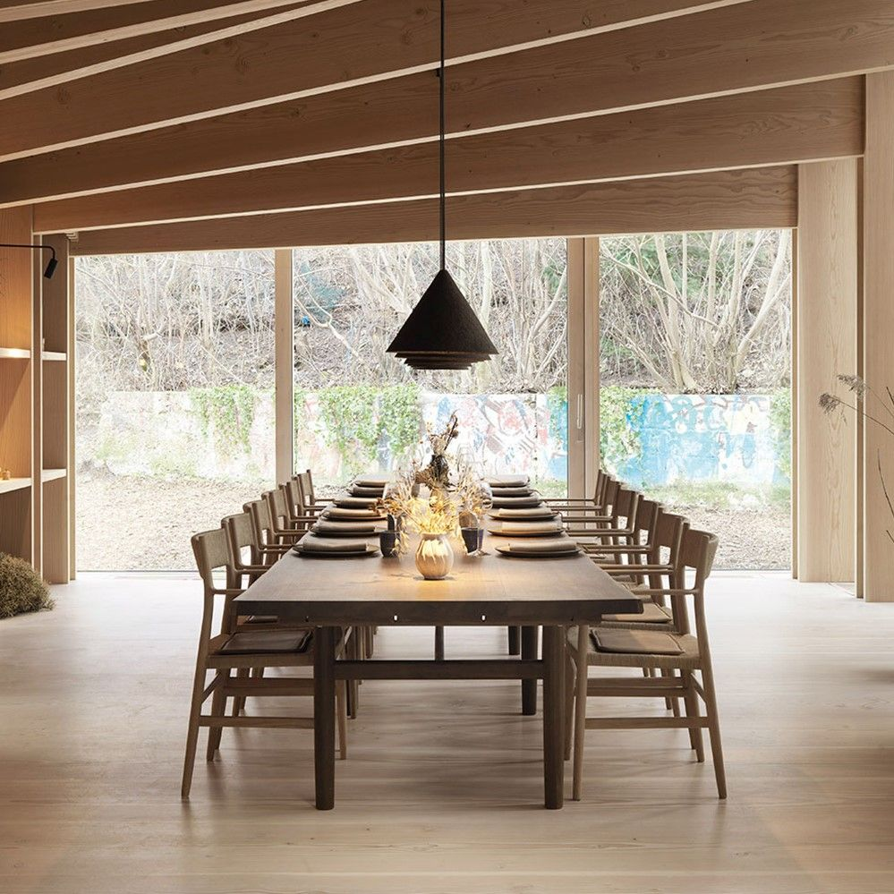 Long restaurant table with wooden chairs featuring cushions crafted with Sørensen Leather