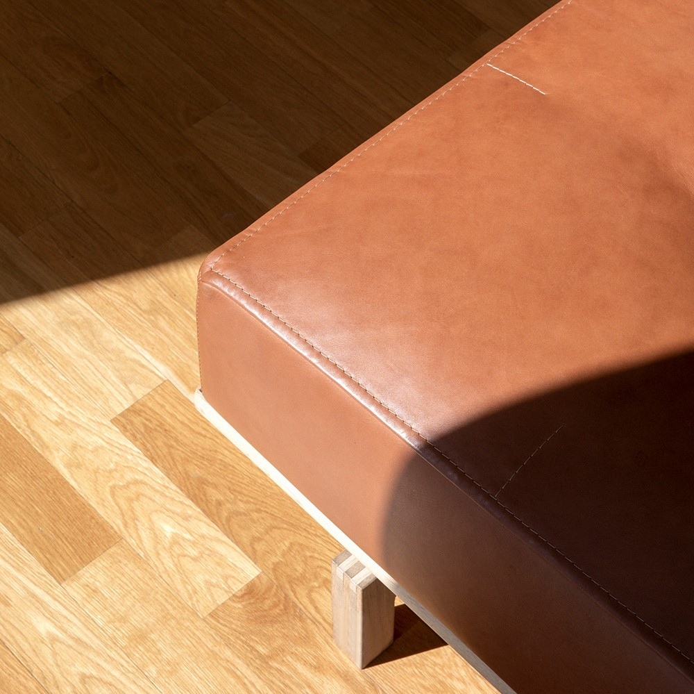 Corner of brown leather sofa with wooden frame