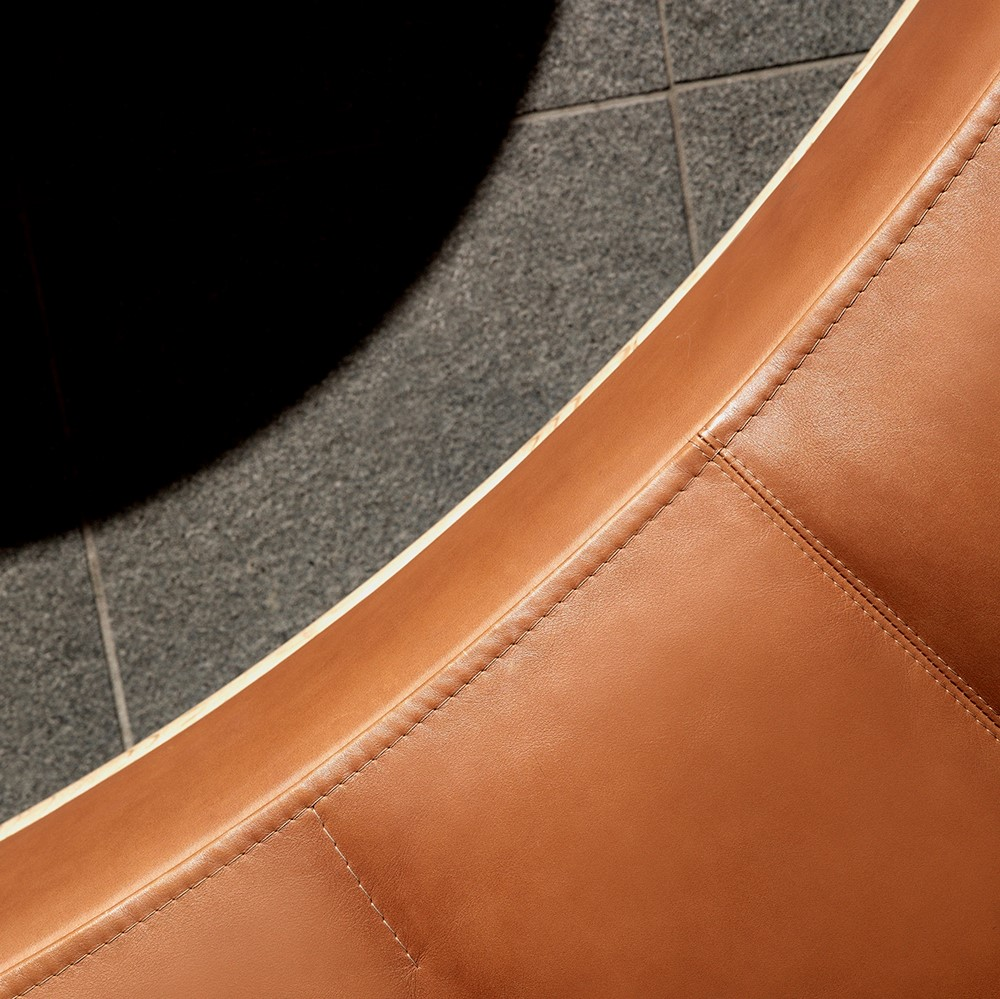 Sewing details of round, brown leather sofa