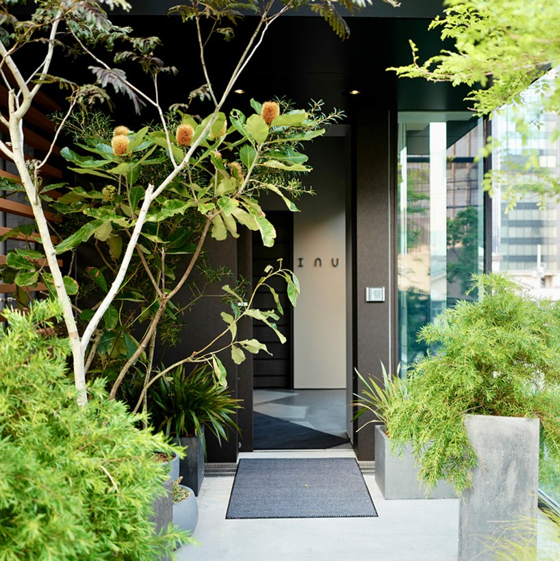 Entrance to INUA in Tokyo with green plants and concrete flower pots