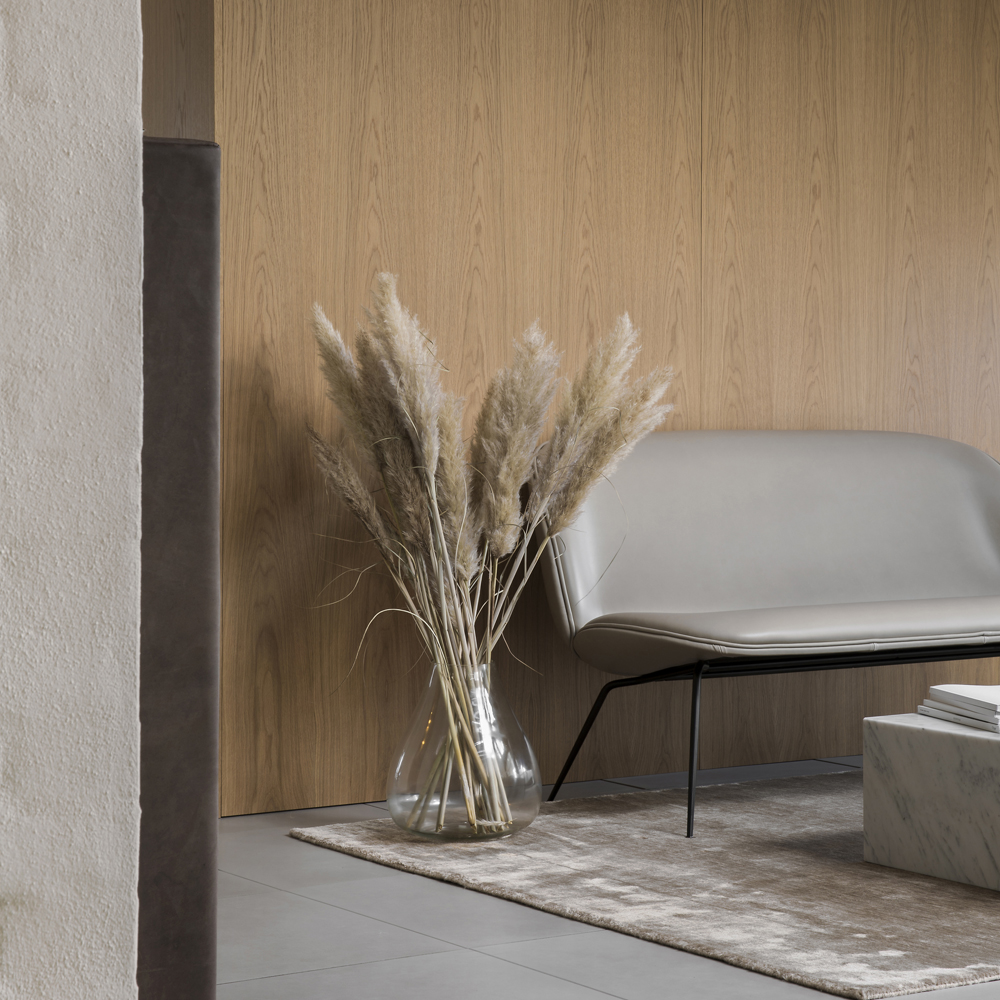 Inside Sørensen Leather HQ decorated with a light grey leather sofa in front of a wooden wall