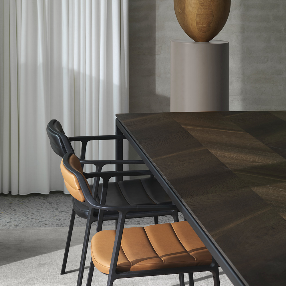 Close-up of dinning room chairs crafted in brown leather around dark wooden dinning table