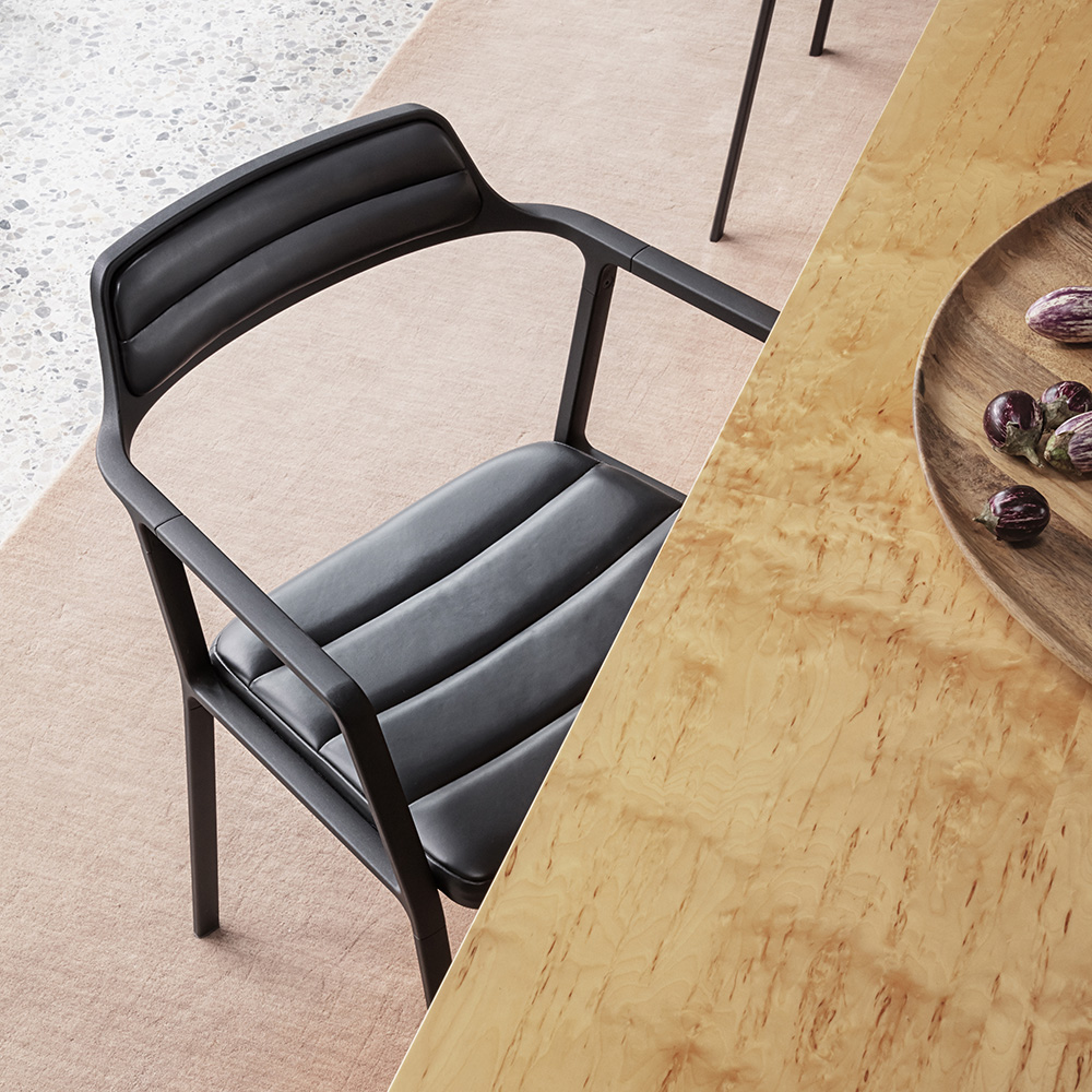 Close-up of dinning room chair crafted in black leather next to wooden dinning table