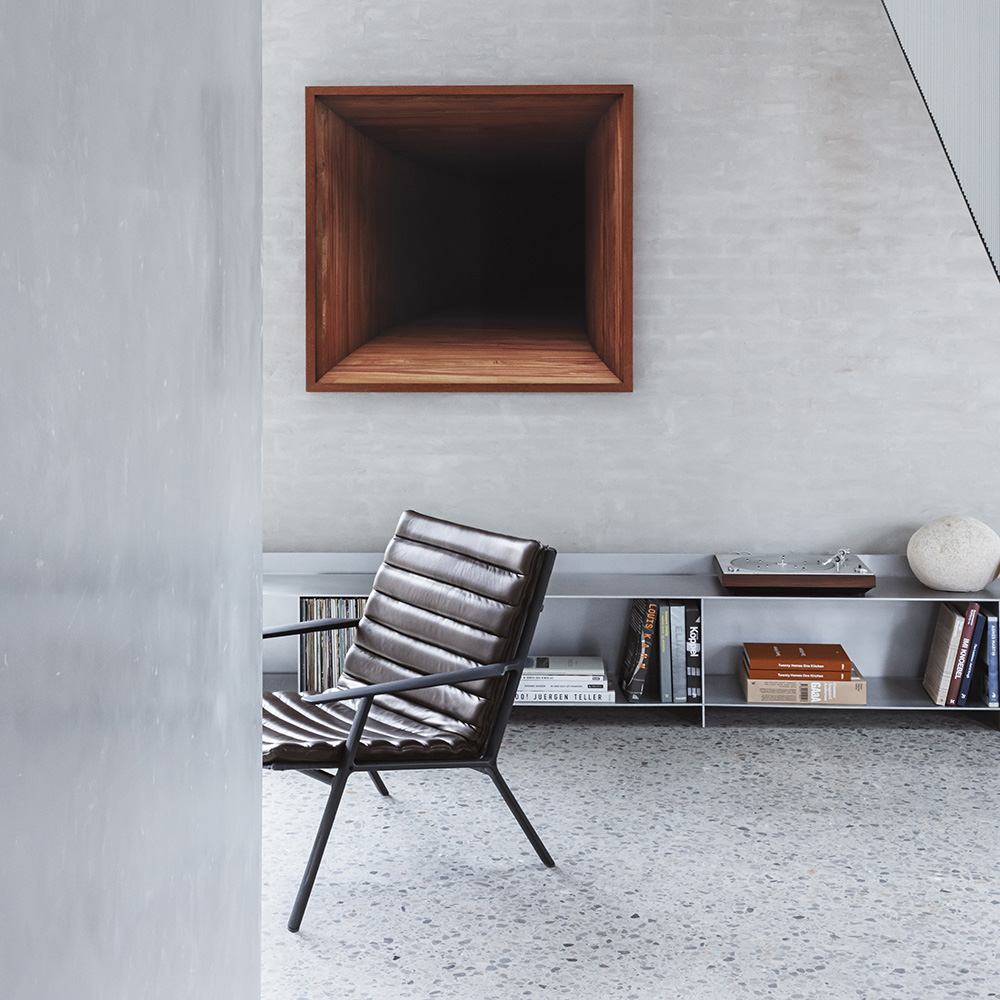 Room in grey concrete with black leather armchair