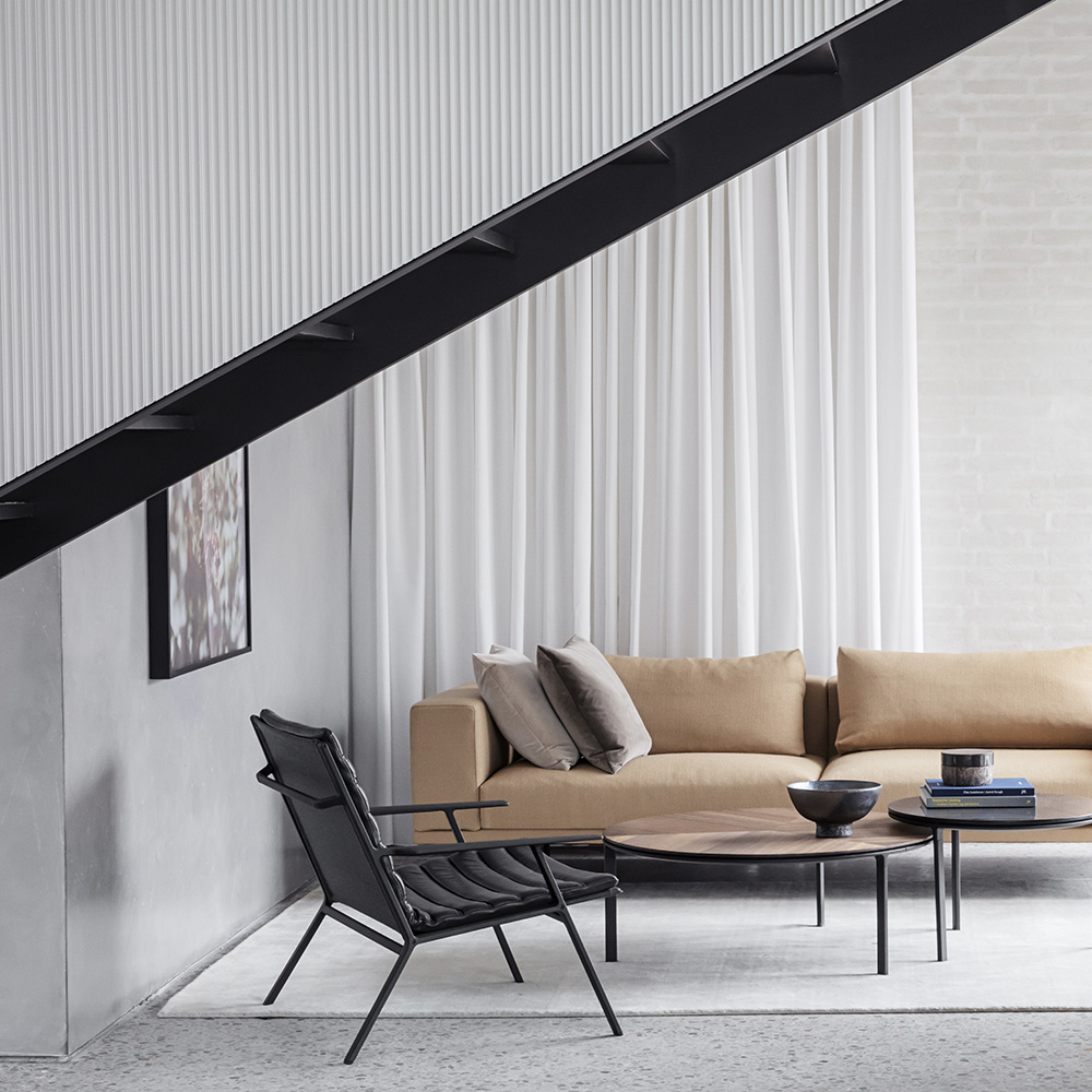 Living room with a brown leather couch and black leather armchair