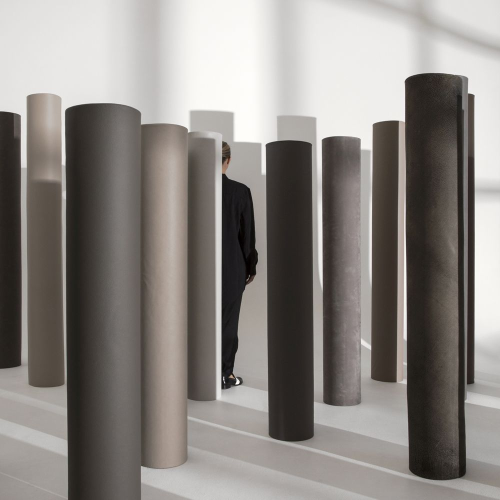 Woman walking among pillars upholstered in brown leather