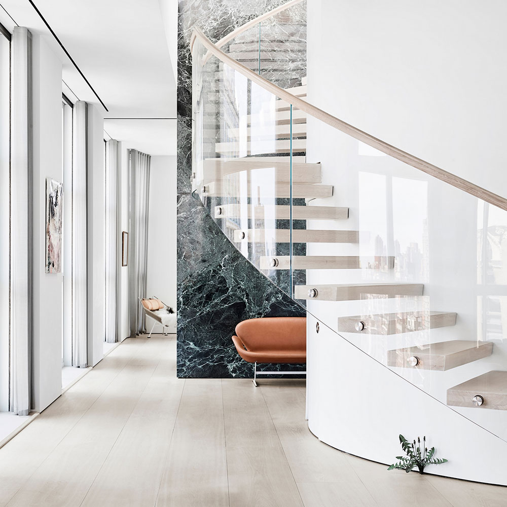 Hallway with a glass staircase and brown leather sofa