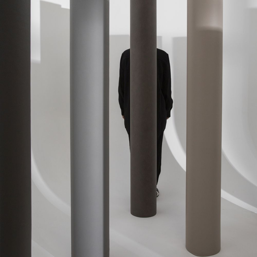 Woman standing behind pillars upholstered in brown leather
