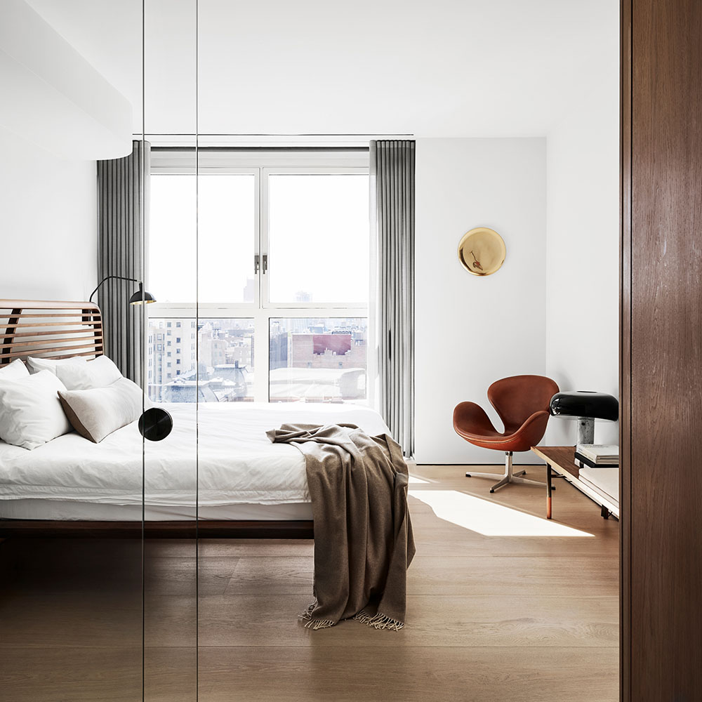 Hotel room overlooking New York with red Swan™ chair by Arne Jacobsen