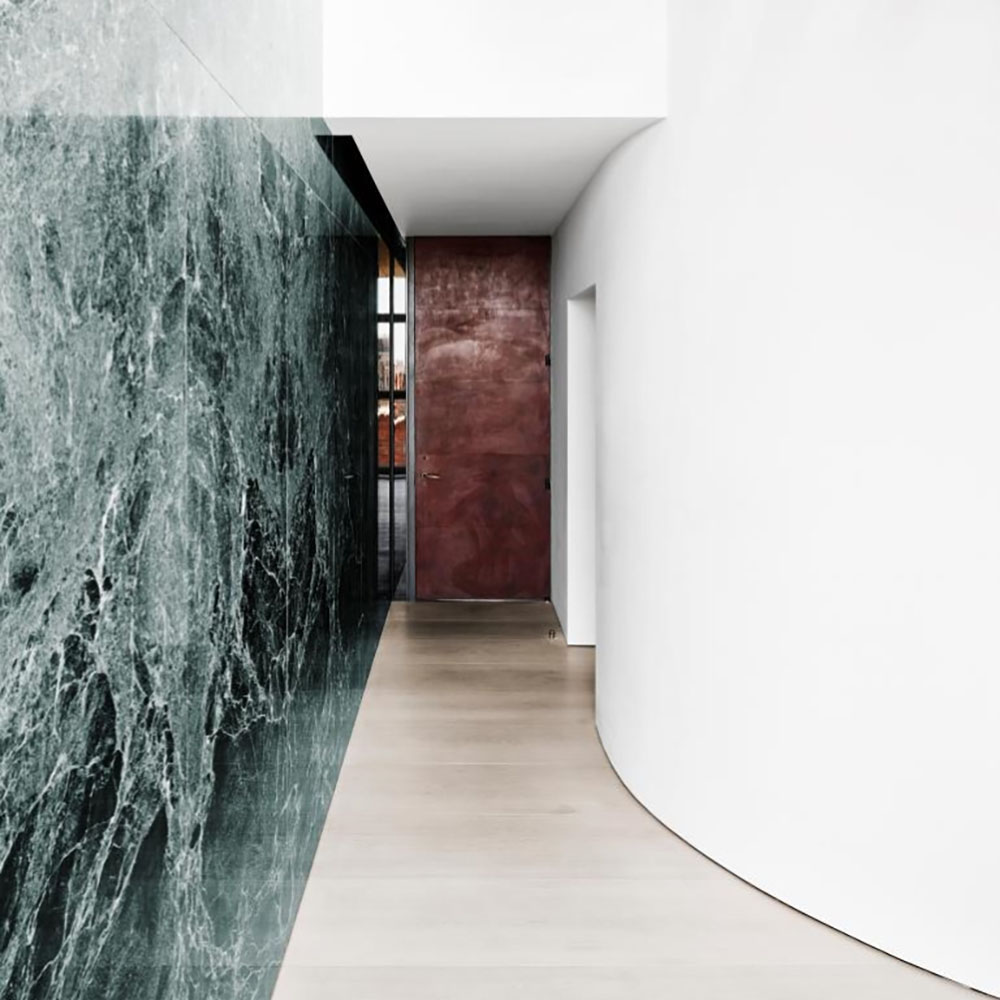 Penthouse hallway with green marble walls and wooden floors