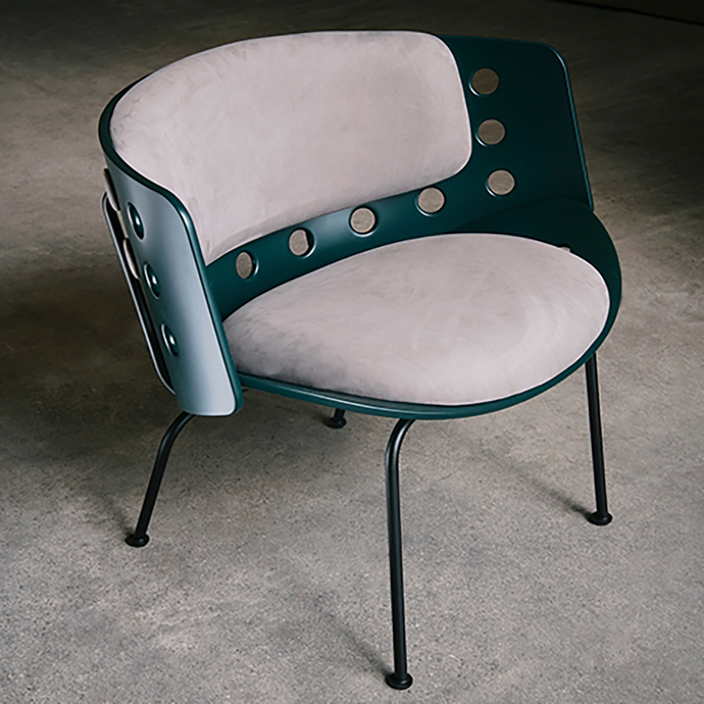 Rounded chair with leather cushioning in a light colour