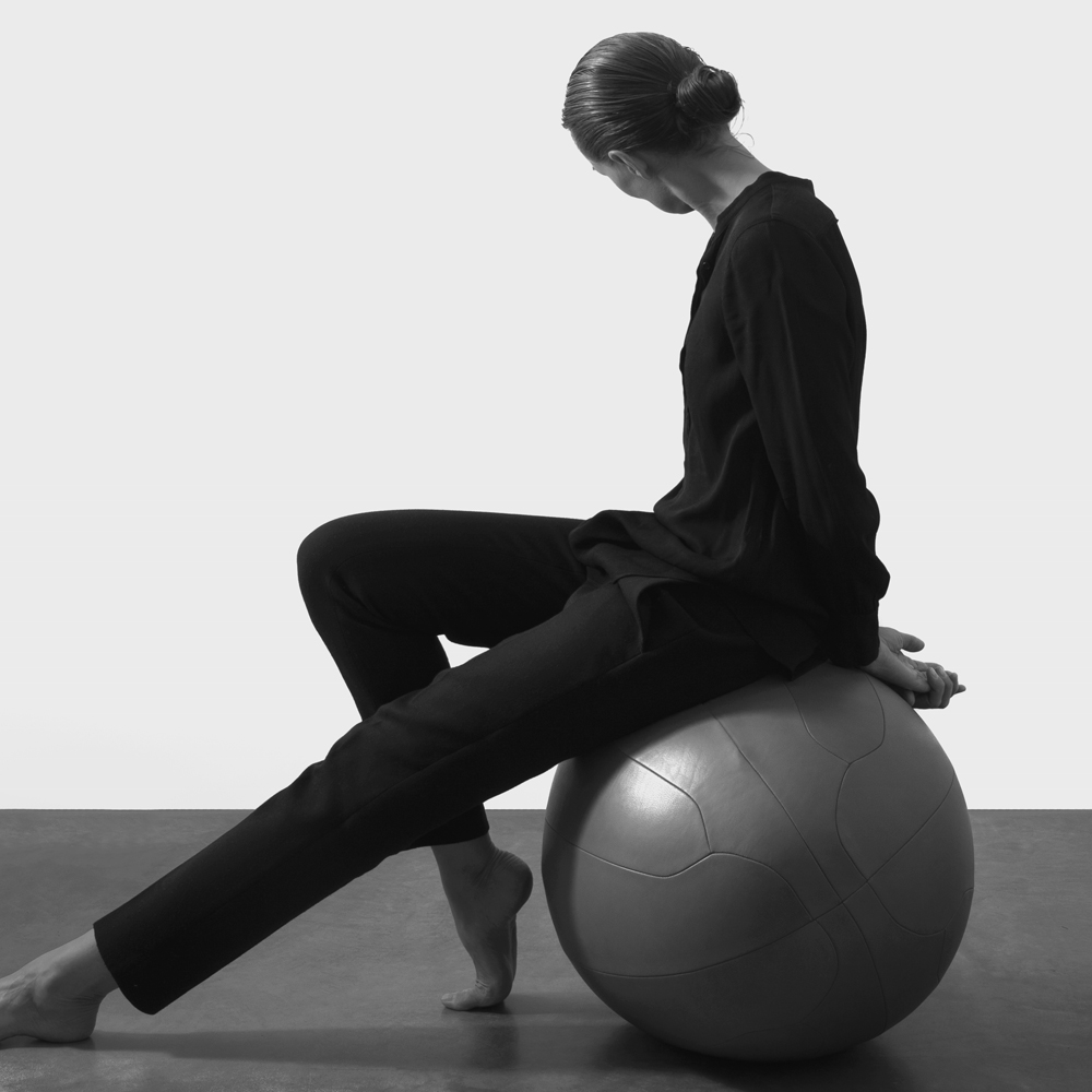 Woman wearing black sitting on an oval ball co-created with SPACE Copenhagen crafted in our NUANCE leather