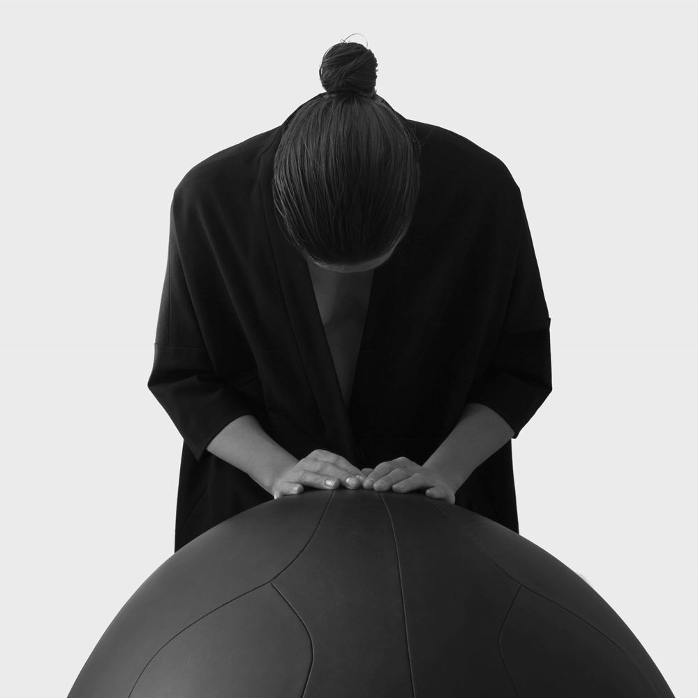 Woman standing with her hands on an oval ball co-created with SPACE Copenhagen crafted in our NUANCE leather