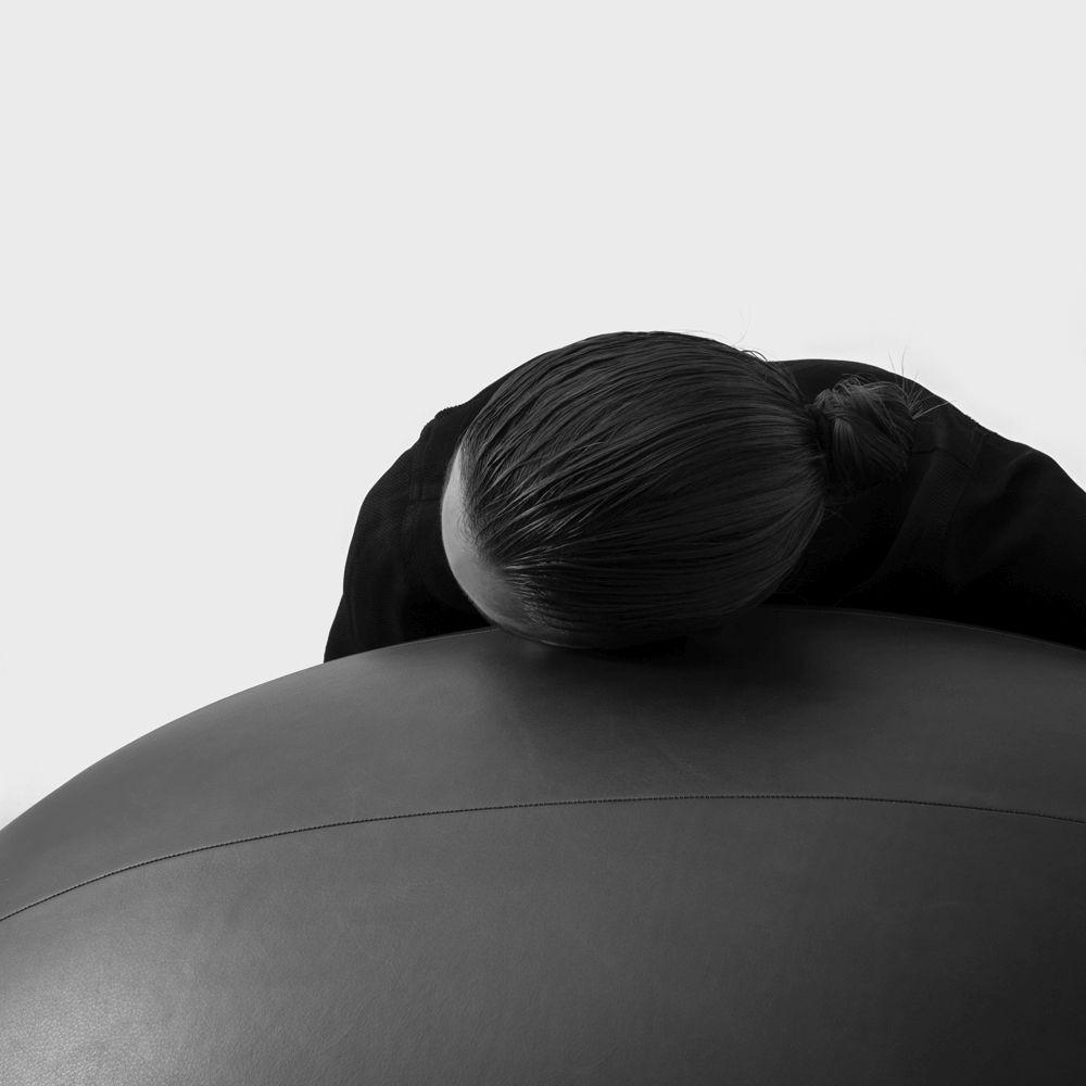 Woman resting her head on an oval ball co-created with SPACE Copenhagen crafted in dark grey leather