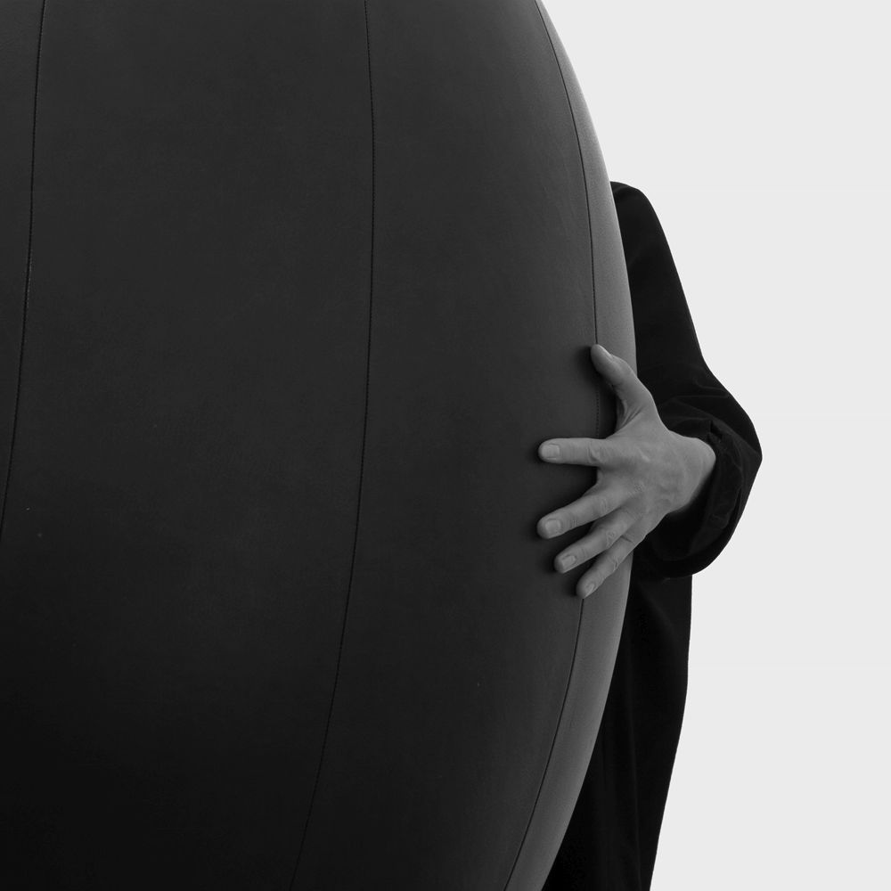 Woman standing with an oval ball in dark grey leather